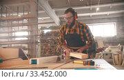 Купить «Bearded man putting on headphones and starts cutting the plywood», видеоролик № 33452000, снято 2 июня 2020 г. (c) Константин Шишкин / Фотобанк Лори