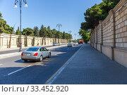 Купить «Movement of cars on a busy street. Soundproof fence», фото № 33452920, снято 27 сентября 2019 г. (c) Евгений Ткачёв / Фотобанк Лори
