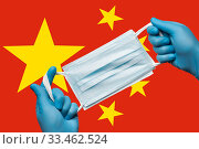 Medic holding respiratory face mask in hands in blue gloves on background flag of People's Republic of China PRC. Стоковое фото, фотограф А. А. Пирагис / Фотобанк Лори