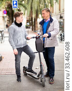 Man talking to teenage son with scooter outdoors. Стоковое фото, фотограф Яков Филимонов / Фотобанк Лори