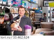 Portrait of happy man with his chihuahua dog visiting pet supplies shop. Стоковое фото, фотограф Яков Филимонов / Фотобанк Лори