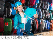 positive girl chooses a backpack for camping in the sports shop. Стоковое фото, фотограф Яков Филимонов / Фотобанк Лори