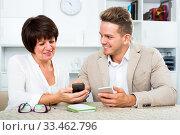 Купить «Mother and son with smartphones», фото № 33462796, снято 8 июля 2020 г. (c) Яков Филимонов / Фотобанк Лори
