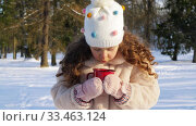 Купить «little girl with cup of hot tea in winter park», видеоролик № 33463124, снято 9 марта 2020 г. (c) Syda Productions / Фотобанк Лори
