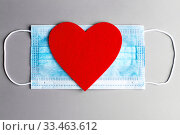 Купить «Medical mask on a light gray background with a big scarlet heart», фото № 33463612, снято 16 марта 2020 г. (c) Геннадий Байдин / Фотобанк Лори
