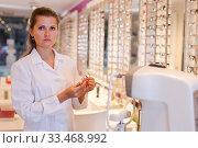 Купить «Female optometrist offering glasses», фото № 33468992, снято 27 августа 2019 г. (c) Яков Филимонов / Фотобанк Лори