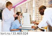 Купить «Two optometrists testing eyesight of woman», фото № 33469024, снято 27 августа 2019 г. (c) Яков Филимонов / Фотобанк Лори