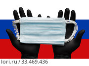 Купить «Doctor holding respiratory face mask in hands in blue gloves on background flag of Russia. Concept coronavirus quarantine, grippe, pandemic outbreak, protection and epidemic», фото № 33469436, снято 25 марта 2020 г. (c) А. А. Пирагис / Фотобанк Лори