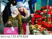 Купить «Young girl and her mother are buying Christmas ornamentals in the market outdoor.», фото № 33474824, снято 19 декабря 2017 г. (c) Яков Филимонов / Фотобанк Лори