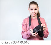 Купить «Young girl with professional dlsr camera in hands, portrait, looking at camera, copyspace», фото № 33479016, снято 31 марта 2020 г. (c) Кекяляйнен Андрей / Фотобанк Лори