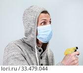 Man wearing hoodie and medical facial mask holding spray cleaner in hand, a grey background. Стоковое фото, фотограф Кекяляйнен Андрей / Фотобанк Лори