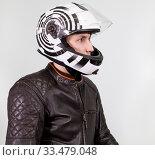 Portrait of motorcyclist man wearing moto helmet, leather jacket. Side view, grey background. Стоковое фото, фотограф Кекяляйнен Андрей / Фотобанк Лори