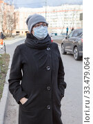 Portrait of an European woman in glasses and one-use mask, looking at camera standing outdoor. Стоковое фото, фотограф Кекяляйнен Андрей / Фотобанк Лори
