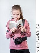 Teen age girl reading service manual book for dlsr camera, beginner in learning photography, a grey background. Стоковое фото, фотограф Кекяляйнен Андрей / Фотобанк Лори