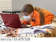 Девочка смешно сидит на кровати в домашней одежде и удаленно учится в школе. Стоковое фото, фотограф Иванов Алексей / Фотобанк Лори