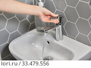 close up of woman's hand opening water tap. Стоковое фото, фотограф Syda Productions / Фотобанк Лори