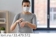 Купить «close up of woman in mask spraying hand sanitizer», фото № 33479572, снято 13 марта 2020 г. (c) Syda Productions / Фотобанк Лори