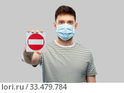 Купить «young man girl in medical mask showing stop sign», фото № 33479784, снято 21 марта 2020 г. (c) Syda Productions / Фотобанк Лори