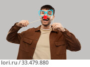 Купить «happy smiling man with glasses and red clown nose», фото № 33479880, снято 22 февраля 2020 г. (c) Syda Productions / Фотобанк Лори