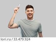Купить «smiling young man holding lighting bulb», фото № 33479924, снято 21 марта 2020 г. (c) Syda Productions / Фотобанк Лори