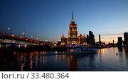 Купить «Evening Moscow. Hotel Ukraine, Novoarbatsky bridge, and a tourist boat at sunset. Russia», видеоролик № 33480364, снято 3 апреля 2020 г. (c) Наталья Волкова / Фотобанк Лори