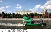 Купить «View of the Kremlin and a modern green tourist boat floating on the Moscow river, Moscow, Russia», видеоролик № 33480372, снято 3 апреля 2020 г. (c) Наталья Волкова / Фотобанк Лори