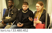 Купить «Portrait of casual people wearing warm jackets riding subway on way to work on winter day», видеоролик № 33480452, снято 17 января 2020 г. (c) Яков Филимонов / Фотобанк Лори