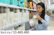 Купить «Asian female customer choosing hair dye in hair care products shop», видеоролик № 33480480, снято 26 мая 2020 г. (c) Яков Филимонов / Фотобанк Лори