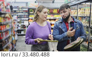 Купить «Young family couple standing near refrigeration showcase in supermarket, choosing frozen pizza», видеоролик № 33480488, снято 29 июня 2020 г. (c) Яков Филимонов / Фотобанк Лори