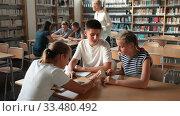 Купить «Teenage students working in groups in college library», видеоролик № 33480492, снято 24 сентября 2019 г. (c) Яков Филимонов / Фотобанк Лори