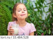 Купить «The girl drank kefir or milk from a glass and licks her tongue with her lips. Kefir mustache», фото № 33484528, снято 1 апреля 2020 г. (c) Екатерина Кузнецова / Фотобанк Лори