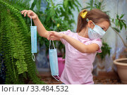 Купить «A little girl in a medical mask disgustedly and with disgust holds another mask in her hands», фото № 33484532, снято 1 апреля 2020 г. (c) Екатерина Кузнецова / Фотобанк Лори