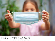 Little girl holds a medical mask in outstretched hands. The child puts on a protective mask. Стоковое фото, фотограф Екатерина Кузнецова / Фотобанк Лори