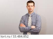 Купить «A worker in a cage shirt and tie crossed his hands on his chest. half-length portrait», фото № 33484852, снято 4 апреля 2020 г. (c) Владимир Арсентьев / Фотобанк Лори