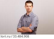 Купить «A worker in a cage shirt and tie crossed his hands on his chest. half-length portrait», фото № 33484908, снято 4 апреля 2020 г. (c) Владимир Арсентьев / Фотобанк Лори