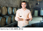 Owner of winery standing with wine in cellar. Стоковое фото, фотограф Яков Филимонов / Фотобанк Лори