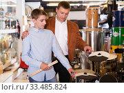 Купить «Boy and father choosing best drum», фото № 33485824, снято 29 марта 2017 г. (c) Яков Филимонов / Фотобанк Лори