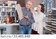 Купить «Glad young customers choosing kitchen facade», фото № 33485848, снято 4 апреля 2017 г. (c) Яков Филимонов / Фотобанк Лори