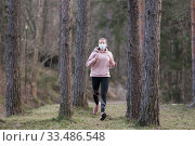 Купить «Corona virus, or Covid-19, is spreading all over the world. Portrait of caucasian sporty woman wearing a medical protection face mask while running in nature.», фото № 33486548, снято 28 марта 2020 г. (c) Matej Kastelic / Фотобанк Лори