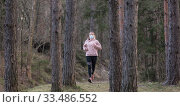 Купить «Corona virus, or Covid-19, is spreading all over the world. Portrait of caucasian sporty woman wearing a medical protection face mask while running in nature.», фото № 33486552, снято 28 марта 2020 г. (c) Matej Kastelic / Фотобанк Лори