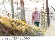 Купить «Corona virus, or Covid-19, is spreading all over the world. Portrait of caucasian sporty woman wearing a medical protection face mask while walking in the forest. Corona virus.», фото № 33486560, снято 28 марта 2020 г. (c) Matej Kastelic / Фотобанк Лори