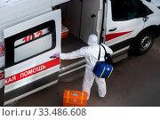 Купить «Врач у автомобиля экстренной службы скорой помощи идет к пациенту с подозрением на новую коронавирусную инфекцию COVID-19 в жилом районе города Москвы, Россия», фото № 33486608, снято 5 апреля 2020 г. (c) Николай Винокуров / Фотобанк Лори