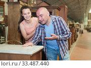 Купить «Cheerful couple looking for vintage drawer chest», фото № 33487440, снято 22 мая 2019 г. (c) Яков Филимонов / Фотобанк Лори