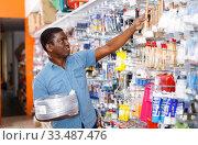 Confident African-American handyman choosing materials for overhauls in household store. Стоковое фото, фотограф Яков Филимонов / Фотобанк Лори