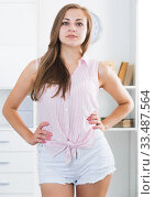 Young woman standing akimbo in room. Стоковое фото, фотограф Яков Филимонов / Фотобанк Лори