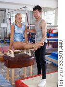Купить «Gymnast in bodysuit training at vaulting buck in sport gym, man helping», фото № 33501440, снято 18 июля 2018 г. (c) Яков Филимонов / Фотобанк Лори