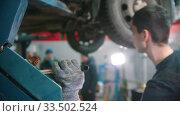 Купить «Auto repair shop - young man worker lifting the car up», видеоролик № 33502524, снято 8 апреля 2020 г. (c) Константин Шишкин / Фотобанк Лори