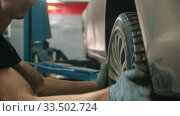 Купить «Auto repair shop - young man in gloves unscrews the wheel off the car», видеоролик № 33502724, снято 8 апреля 2020 г. (c) Константин Шишкин / Фотобанк Лори