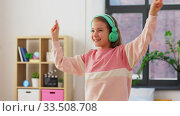 Купить «happy smiling girl in headphones dancing at home», видеоролик № 33508708, снято 27 марта 2020 г. (c) Syda Productions / Фотобанк Лори