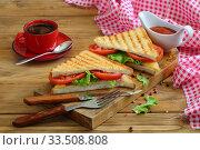 Купить «Sandwich with tomatoes, cheese and ham on a dark, wooden background», фото № 33508808, снято 8 апреля 2020 г. (c) Марина Володько / Фотобанк Лори